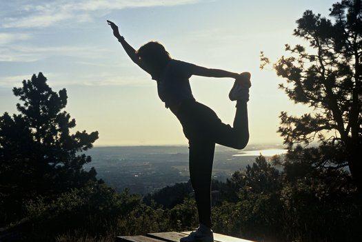 Woman in yoga pose on mountain